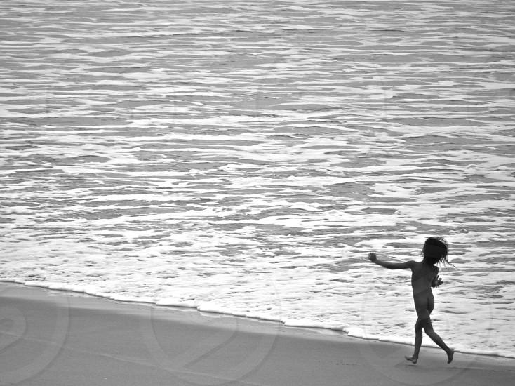 child running by the seashore photo