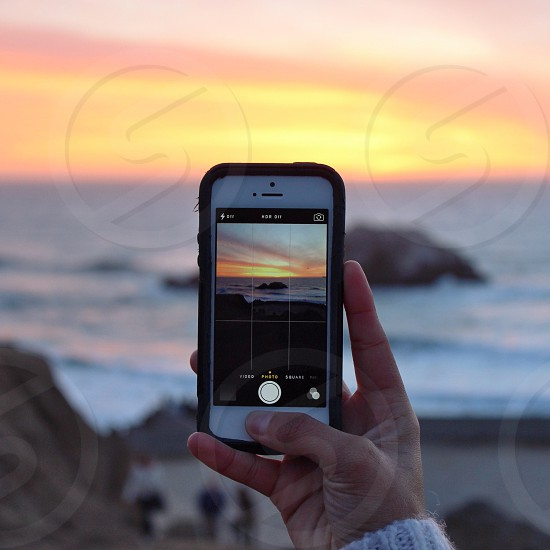 hand holding iphone while taking picture on the ocean photo