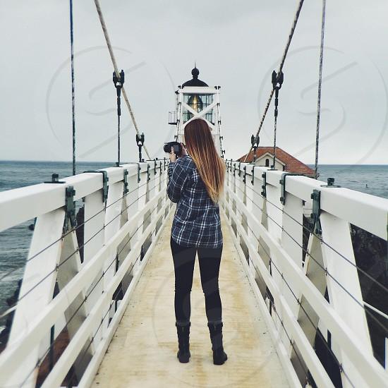 woman stand on a white  wooden bridge photo