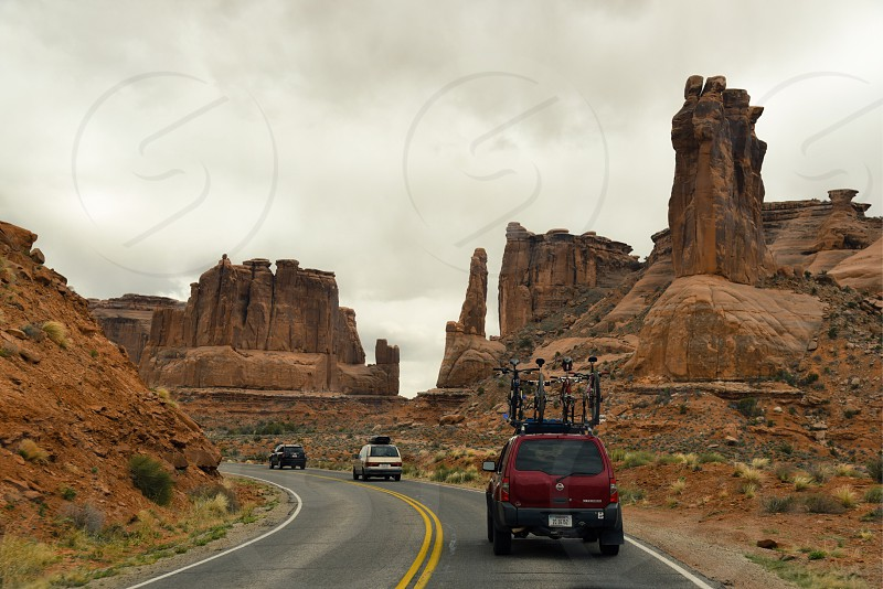 red suv with roof rack carrier running on road near grand canyon arizona under white clouds during daytime photo