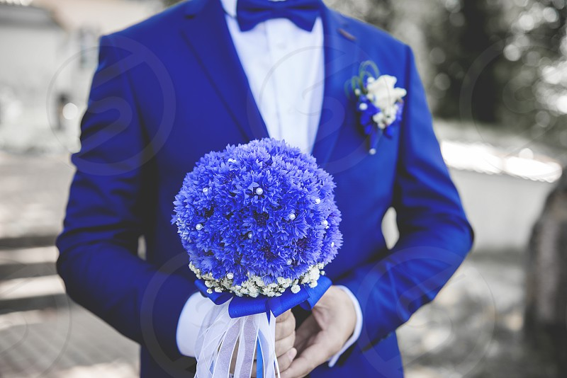 Close up of beautiful bridal bouquet of white and blue cornflowers in groom's hand outdoors copy space. Wedding concept photo