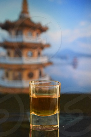 selective focus of glass filled with liqour with pagoda as background photo