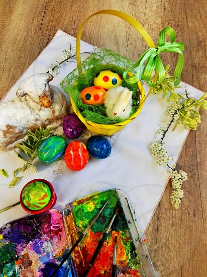 easter tradition painting eggs easter basket and bunny on wooden table photo