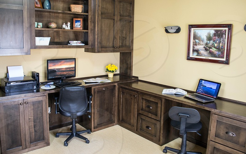 built in full room dark wood desk and cupboards photo