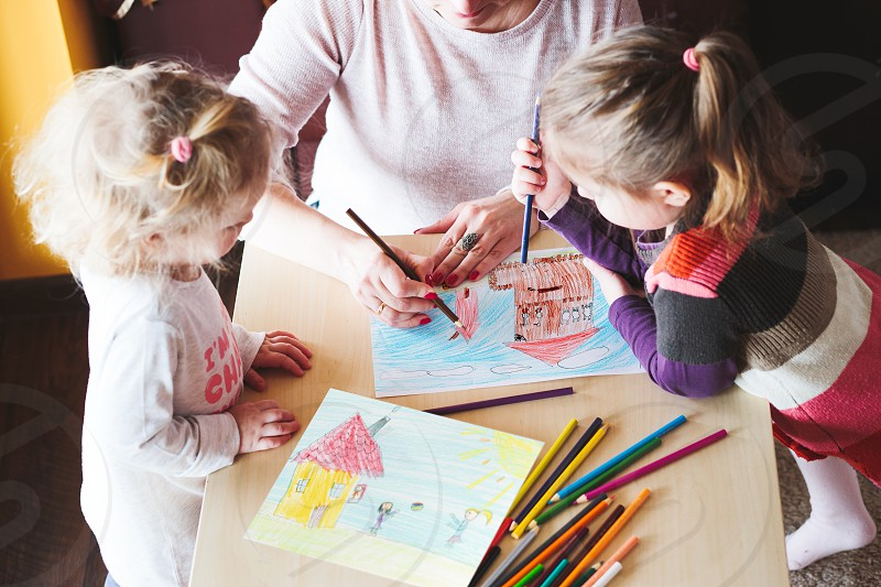 Mom with little girls drawing a colorful pictures of house and playing children using pencil crayons standing at table indoors. Shot from above photo