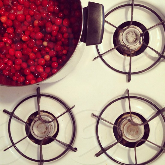 cooking pot with red round fruits on white gas stove photo