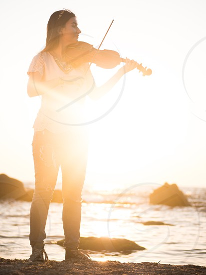 Young beautiful caucasian girl wearing jeans plays violin staying on the beach near the beautiful sea or ocean photo