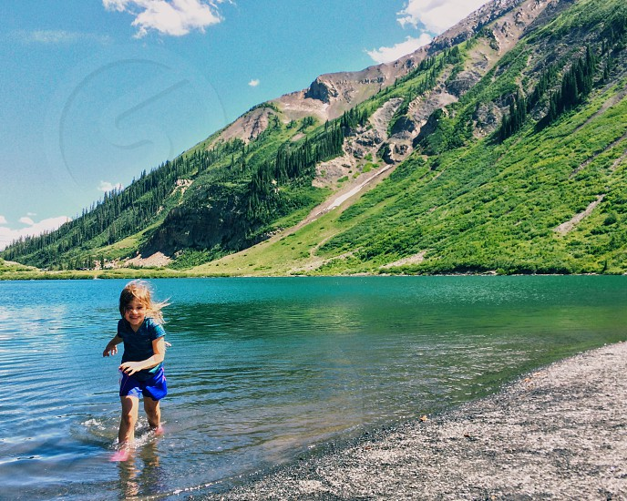 Lake nature mountains water scenic summer vacation camp camping kids children girl family fun play happy splash jumping in water jumping into lake little girl summer camp hike hiking outdoors health healthy brave smile photo
