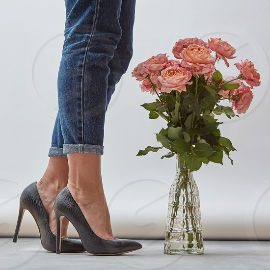 Legs of the girl in elegant black shoes and jeans with a bouquet of pink roses in a transparent vase on a gray background. Layout for your ideas photo