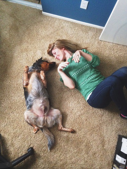 woman beside brown and black long haired dog lying down on brown carpet surface photo