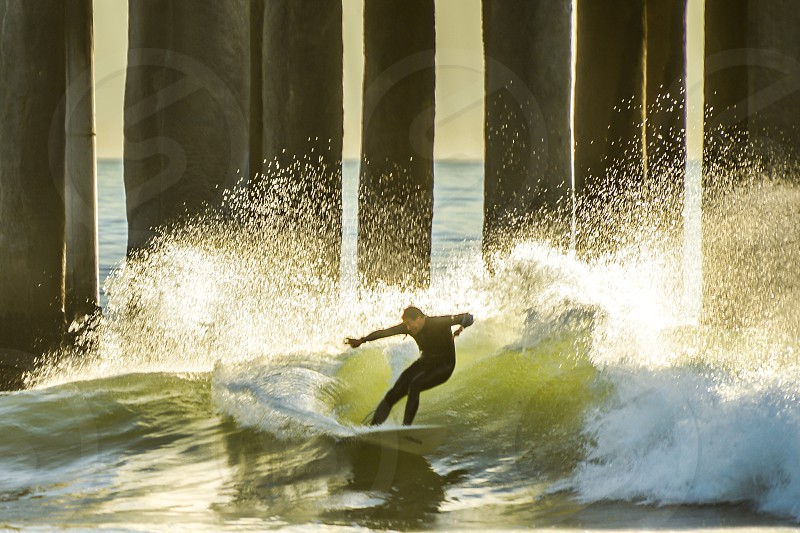 man in black rash guard surfing on sea waves with white surfing board photo