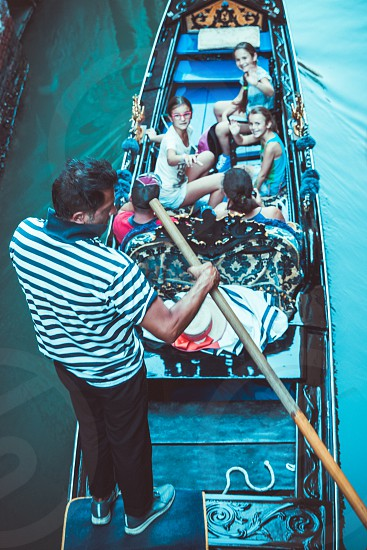 Gondolier Giving A Family Ride With Gondola In Venice Italy photo