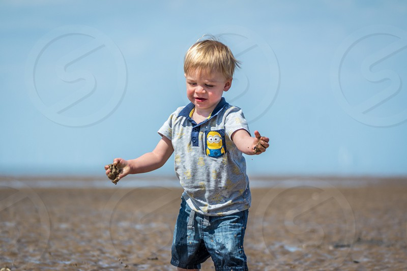 Toddler playing with sand at the beach  photo