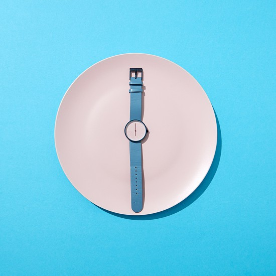 Wristwatch with six o'clock and blue bend on a white plate on a blue background. Time to lose weight eating control or diet concept. Top view. photo