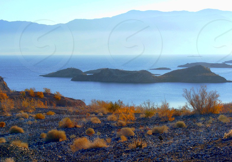 Mist or fog over a small lake  surrounded by hills and grass  with a small island. photo