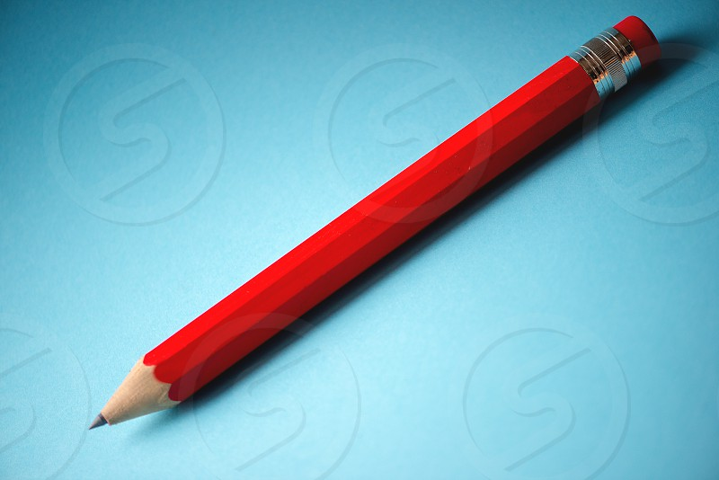 Red pencil on blue background photo