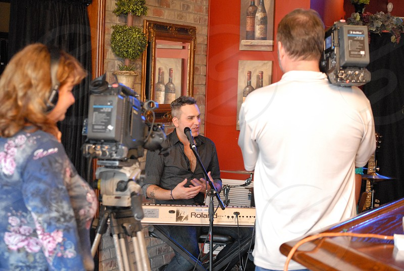 musician filming a tv show indoors with full camera gear photo