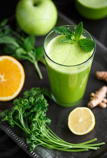 Fresh homemade green juice with orange apple parsley mint and ginger photo