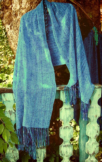 Soft fringed blue shawl draped over a country fence. photo