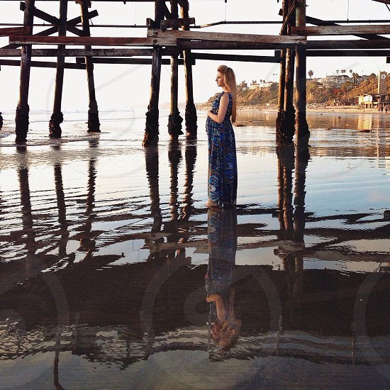 pregnant woman wearing blue long dress near the dock by the beach photo