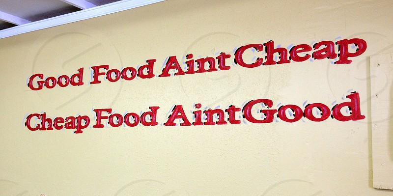"Painted slogan on wall ""Good Food Aint Cheap Cheap Food Aint Good "" photo"