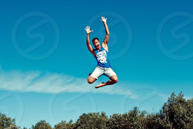 man in blue tank top having jump shot photo taken near trees photo