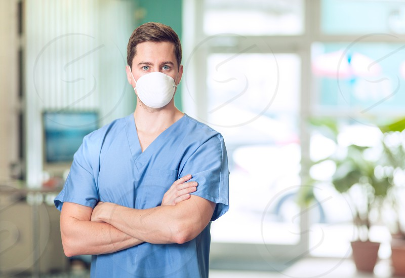 man in blue scrub suit and white mask photo