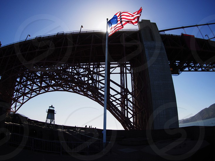 The flag flies at Fort Point under the Golden Gate Bridge photo