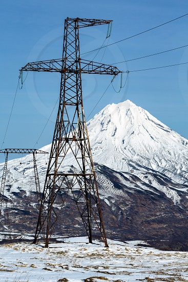 High voltage power line on clear sunny day. View on high voltage metal towers in mountain on background of snowcapped cone of Vilyuchinsky Volcano. Kamchatka Peninsula Russian Far East Eurasia. photo