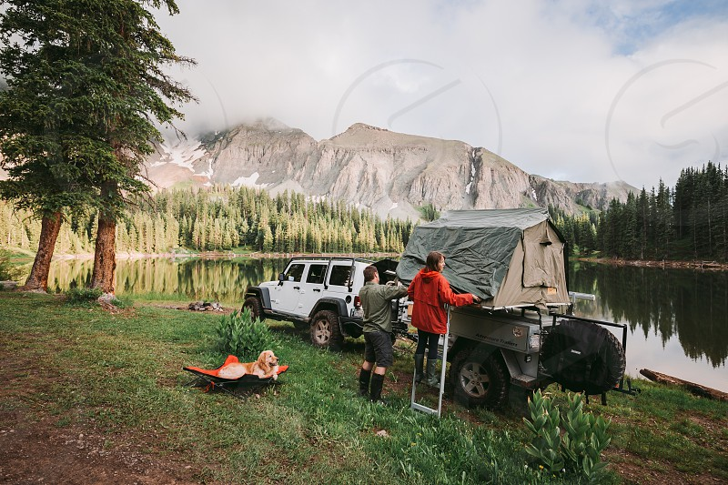 girl in red jacket beside man in gray sweater fixing camping tent on trailer by the lake photo
