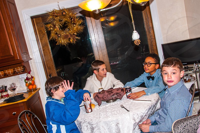group of 4 boys sitting in front of white round table near black flat screen television photo