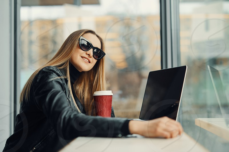 Young girl sit in coffee place in front of the window look at her laptop and drink tea from red cup photo