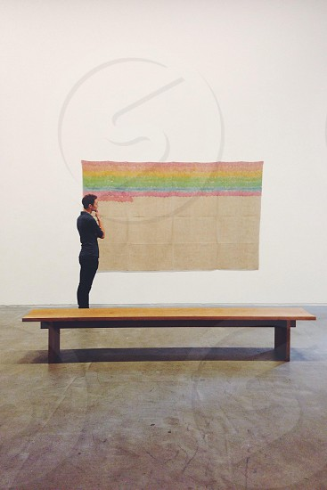 figure in blue shirt at museum looking at rainbow colored painting near wooden bench photo