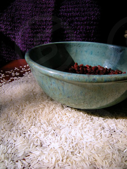 Teal bowl filled with red beans on purple background surrounded by rice photo