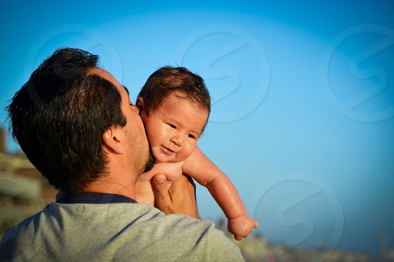 man holding his baby and kiss him over cloudy sky during daytime photo