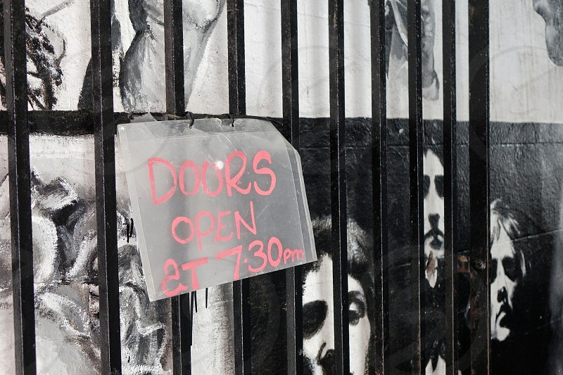 Sign 'doors open at 7.30' on a gate with images of people's head behind... photo