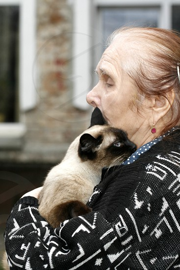 woman in black and white aztec cardigan hugging siamese cat in tilt shift lens photo