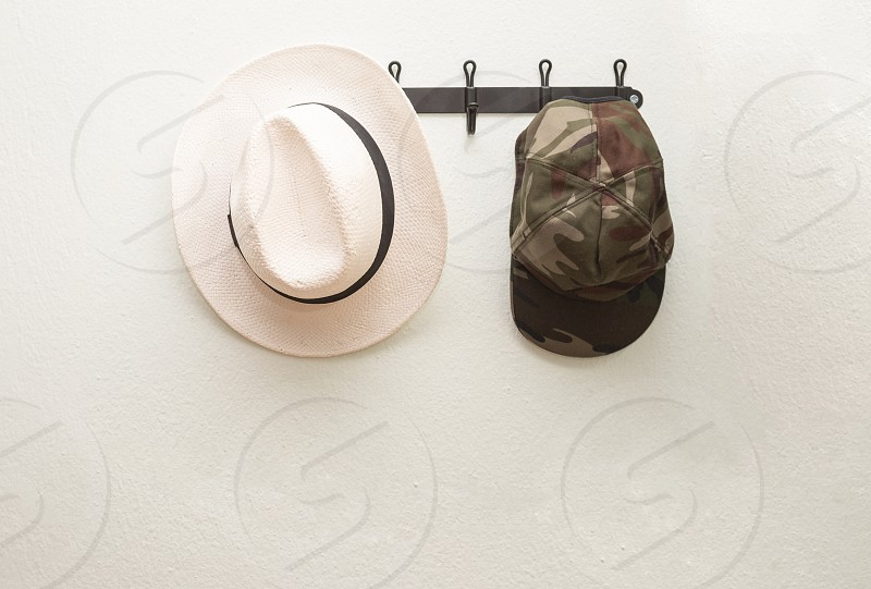 white cowboy hat near green and brown camouflage cap on black steel wall mount rack photo