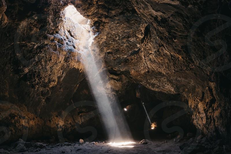 light beams pierce through the dark lava cave  photo