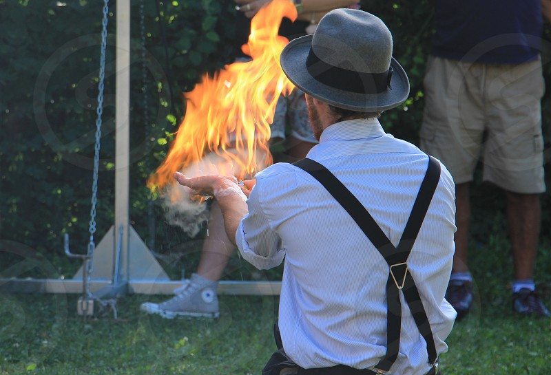 man wearing gray and black bowler cap with fire in hand photo