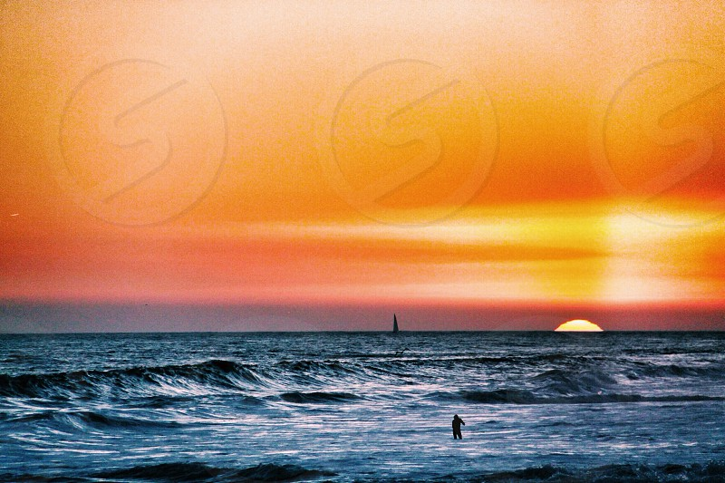 person standing by the sea on a sunset view photo