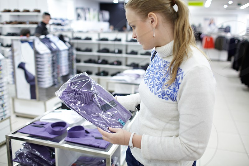Young woman is choosing a shirt for her boyfriend in the department store. photo