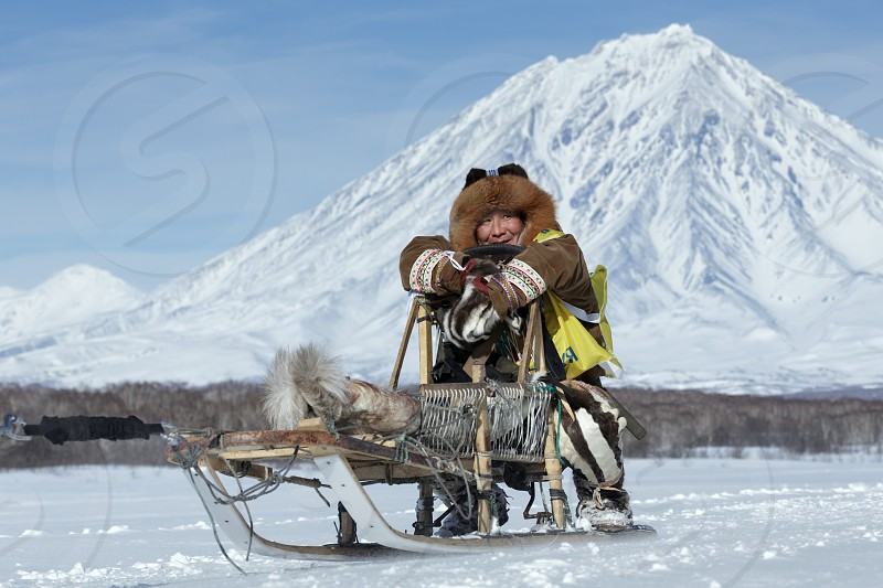 KAMCHATKA RUSSIA - FEB 25 2017: Kamchatka musher Mandyatov Roman dressed in national clothes rides on traditional sled of indigenous peoples of Kamchatka. Kamchatka Sled Dog Racing Beringia Russian Cup of Sled Dog Racing (snow disciplines) photo