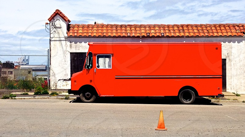Red delivery van in front of old tile-roofed building.  photo