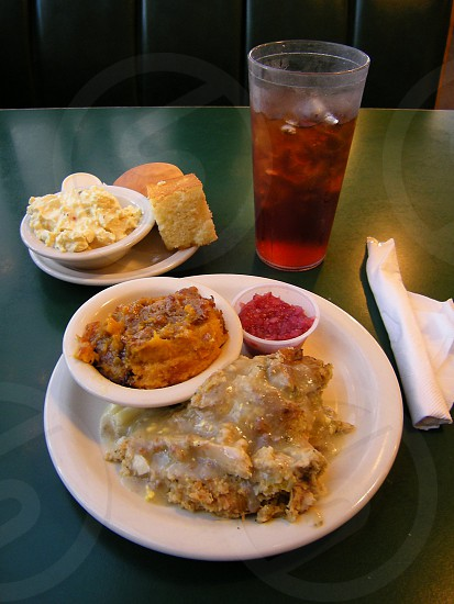 Daily plate lunch special with chicken and dressing sweet potato casserole cranberry sauce deviled egg salad cornbread and roll and tea on green background photo