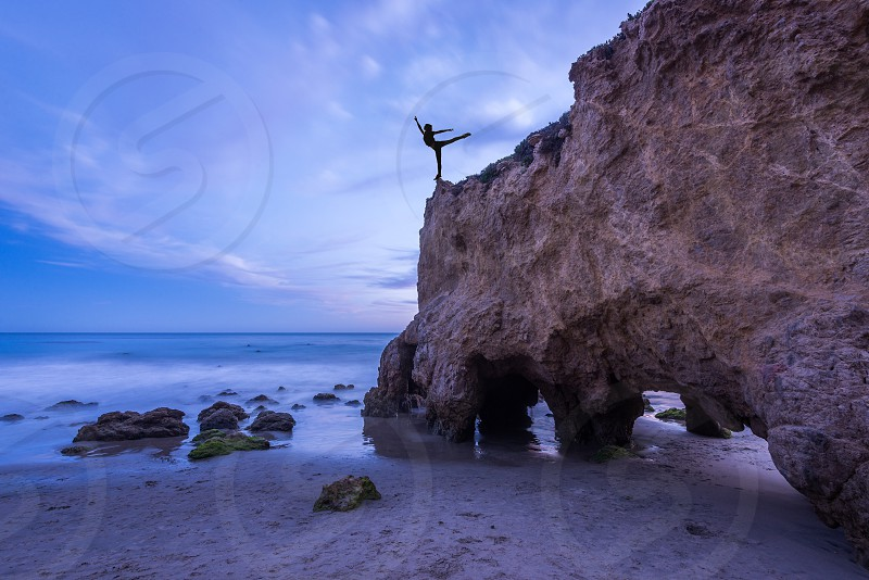 woman meditating on cliff of beach rock formation photo