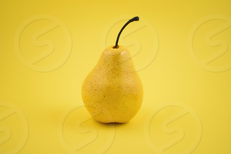 Pear decoration. Yellow pear on a yellow background. Pear home decor. Yellow decorative pear photo