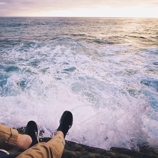 person sitting on rocks near crashing ocean waves photo