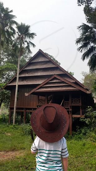 person in gray shirt wearing brown cowboy hat looking at brown wooden house beside coconut trees during daytime photo