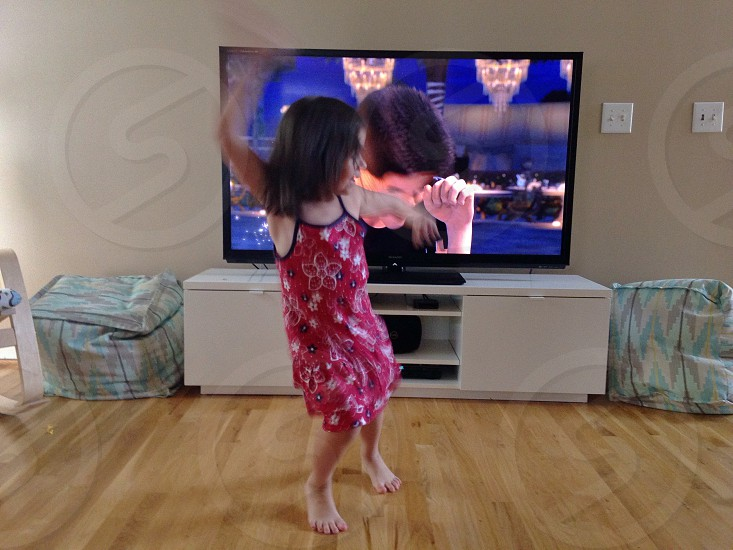 girl in red and black floral dress dancing in front of the tv photo